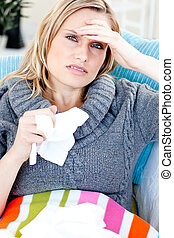 Downcast woman lying on a sofa with tissues and feeling her temperature against a white background