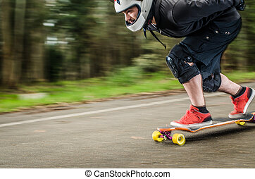 Downhill skateboarder in action on a asphalt road.