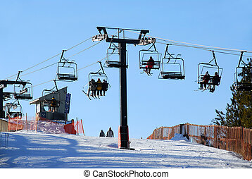 Downhill skiing - Chairlift with skiers on downhill ski...