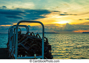 downhill trails from ship at sunset in the sea with ropes