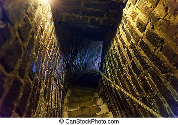 Downstairs in ancient stone tower tunnel