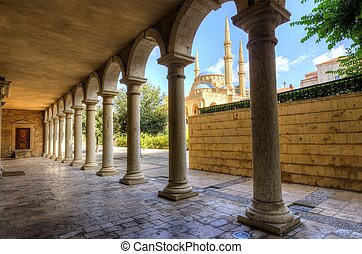 The Mohammad Al-Amin Mosque situated in Downtown Beirut, in Lebanon as viewed through the pillars of the Greek Orthodox church of St George.