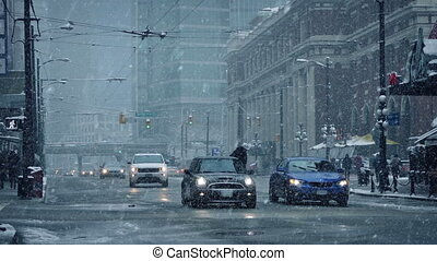 Cars and cyclist on city road in winter snowfall