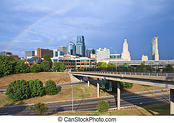 A cityscape view of the downtown Kansas City, Missouri area with a rainbow over the city. Kansas City borders major rivers and is a major city in the Great Plains.
