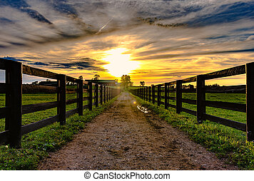 Dirt road leading to a barn in the distance with wooden rail fences on either side with a sunset in the background