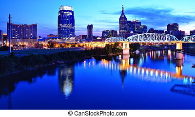 Time Lapse of downtown Nashville, Tennessee, USA from above the Cumberland River at twilight.
