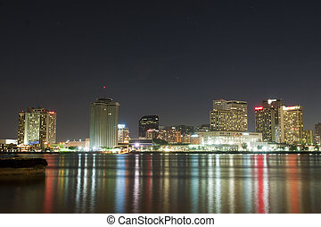 A night image of the lights from downtown New Orleans skyscrapers reflected in the Mississippi River.