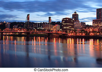 Downtown Portland Oregon at twilight showing the Willamette river, Hawthorne Bridge and building skyline. Photo taken from the East side esplanade