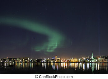 Beautiful scene from dowtown Reykjavik with aurora borealis in the sky above - Reykjavik City hall is the building on the far left and to the right of city hall is Althingi