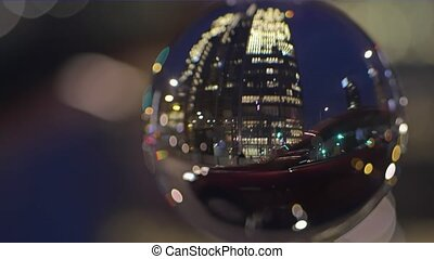 Downtown road traffic and people crossing the street in the evening, view through the glass ball