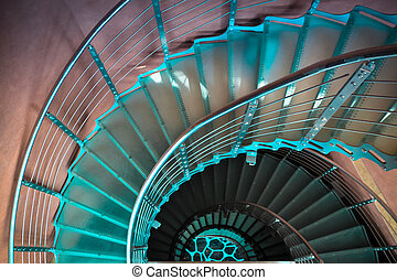 downward spiraling staircase in a  modern tower