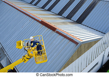 Downward view of woman in cherry picker bucket