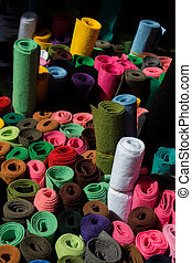 Dozens of colorful fabric rolls in display