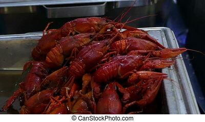 Dozens of red crawfish lie on metallic trays with corn ears...