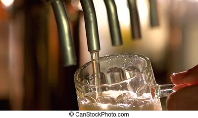 Draft beer pour in a glass, slow-mo. Close up flowing lager...