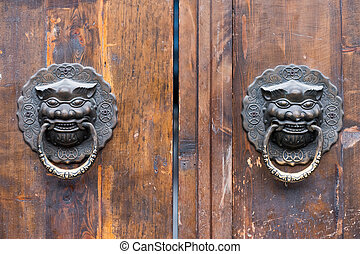 Dragon chinese door knocker on an old wooden gate