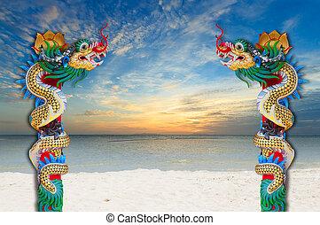 Dragon statue on sand beach at dawn
