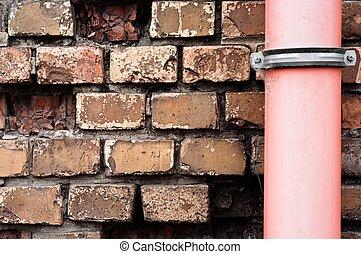 Drain pipe against brick wall
