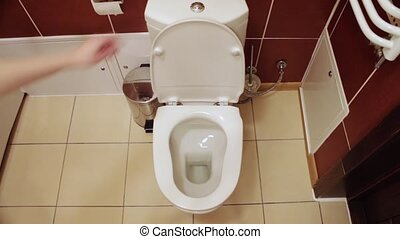WC in White toilet is installed. A man pushes a button and drain drains water inside the toilet bowl