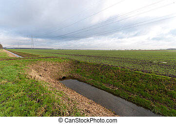 dutch landscape with ditch and some pylons in the background