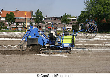 Machine that puts drainage lines into the earth