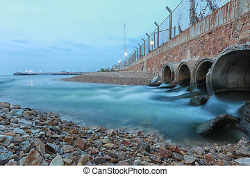 Drainage pipe with water flowing into the sea.