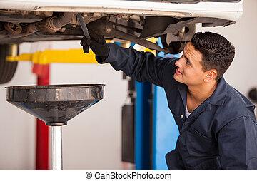 Draining down old engine oil - Young Hispanic mechanic...