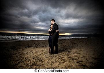 Dramatic Beach Engagement - Loving engaged couple on...