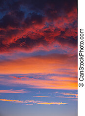 dramatic blue sky with orange clouds at sunset. vertical allignm