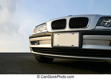 A dramatic shot of the front end of a BMW with the pavement and sky behind