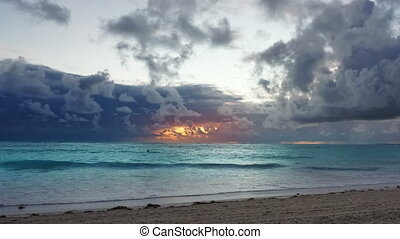 Dramatic caribbean sunrise over ocean waves. Storm