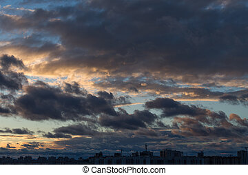 Dramatic cityscape and cloudscape in sunset time with heavy clouds on sky