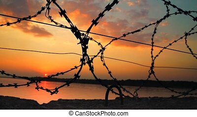 Dramatic clouds behind barbed wire fence