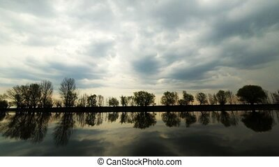 Dramatic clouds on the sky in sunset time. Rain started make choppy water surface with reflections of far riverbank with row of trees. Flood waters of Volga river, Russia