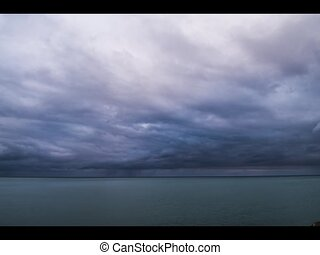 Dramatic Clouds over the water - Stormy dark clouds moving...