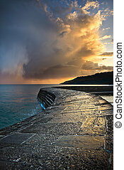 Dramatic Coastal Sunset. A passing storm catching the...