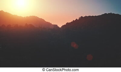 Dramatic colorful mountain sunset. Tropical nature backgrounds. Drone flying over exotic jungle forest hills. Beautiful wild landscape. Camera rise up. Cinematic flight shot orange toning filter