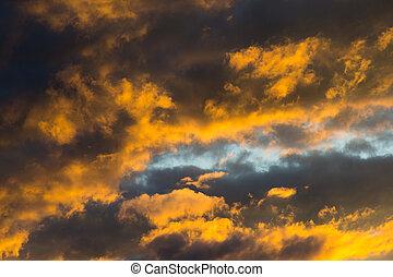 dramatic colorful orange dark cloudscape clouds during sunset