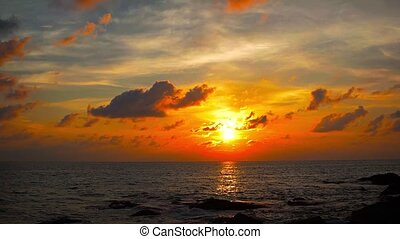Warm, gentle, tropical sea water surges around the rocks and boulders of a beautiful natural beach, as the sun sets in shades of orange and yellow, beneath sparse, puffy clouds.