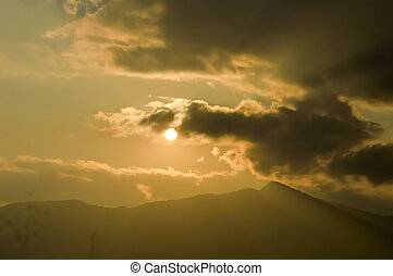 Dramatic dark heavily Red sunset clouds makes the sky romantic on one evening in Mid December. Sunlight reflection through clouds while clouds flying passing rolling or moving over mountain range in a hill station of India. Silhouette
