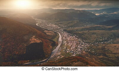 Drone Flight over autumn village in mountain canyon -...