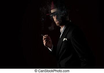 Dramatic fashion model smoking a cigarette while wearing hat