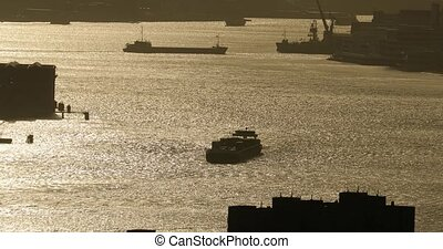 Ship traffic in Rotterdam on the Nieuwe Maas, silhouettes of cargo ships in industrial docks with water glowing with sunlight reflection