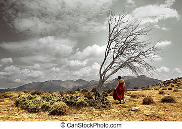 Dramatic landscape with girl and tree