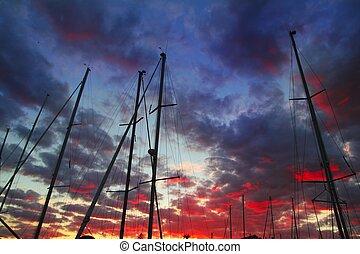 dramatic marina sailboat mast sunset sky backlight