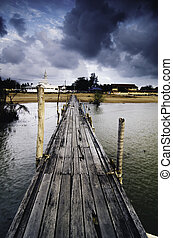 dramatic morning with dark clouds at wooden jetty. sandy beach on the horizon and mosque