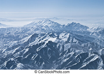 Aerial view of distant snow-capped peaks in the Rockies