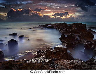 Beautiful ocean seascape with a golden sunset shining through the dark Hawaii purple clouds at twilight