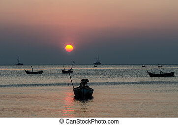 Dramatic of colorful sea and sunset sky with boats