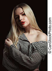 Dramatic portrait of beautiful blonde woman with red lips wearing striped blouse, posing in the dark